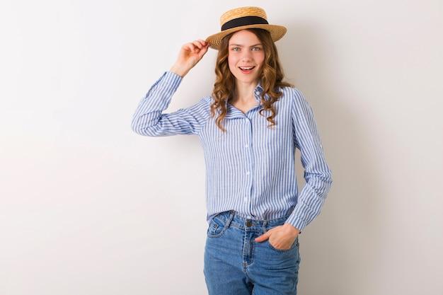 Junge schöne stilvolle frau im sommerart-outfit, das auf weißer wand tragenden strohhut aufwirft
