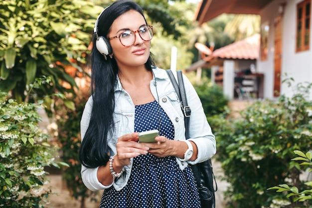 Junge schöne stilvolle frau mit smartphone, kopfhörer, brille, sommer, vintage-denim-outfit, lächelnd, glücklich, positiv