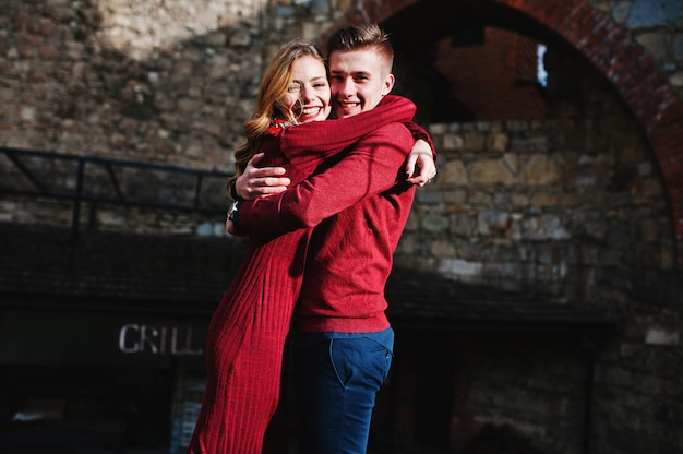 Junge schöne stilvolle modepaare in einem roten kleid in der liebesgeschichte an der alten stadt