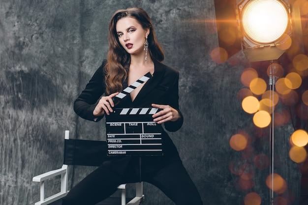 Junge schöne stilvolle sexy frau auf kino hinter der bühne, filmklöppel haltend