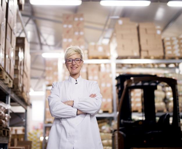 Junge schöne stolze arbeiterin hält ihre arme verschränkt und lächelt für die kamera neben dem gabelstapler in einem fabriklagerraum.