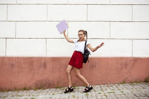 Junge schöne studentin in gläsern, die straße gehen und ordner halten.