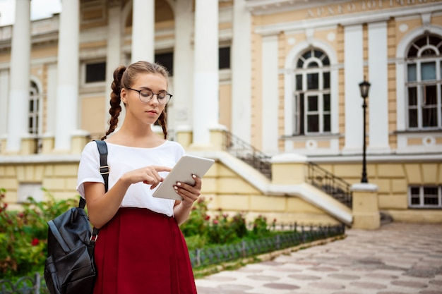 Junge schöne studentin in gläsern, die tablette im freien betrachten.