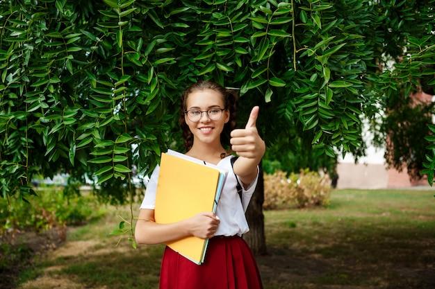 Junge schöne studentin in gläsern lächelnd, daumen hoch zeigend. draußen.