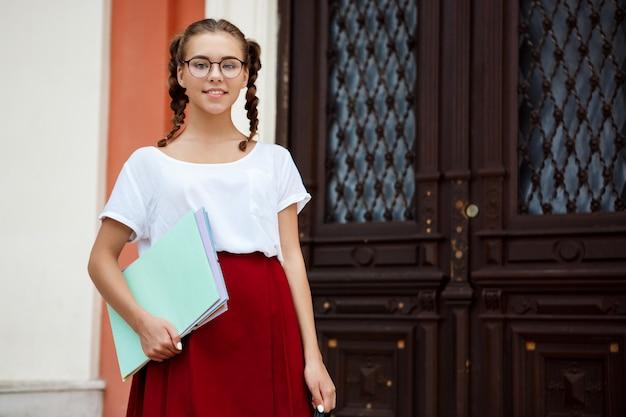 Junge schöne studentin in gläsern lächelnd, ordner im freien haltend.