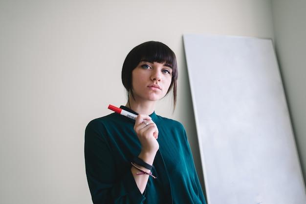 Junge schöne studentin mit markierungsschreiben oder zeichnen steht am whiteboard. sie wird schreiben