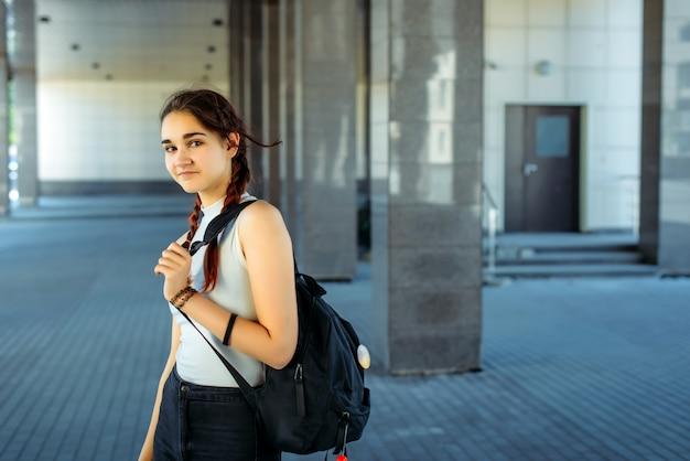 Junge schöne studentin mit rucksack auf der schulter geht zur schule, nahaufnahme. schulmädchen mit zwei zöpfen, die vor dem college stehen