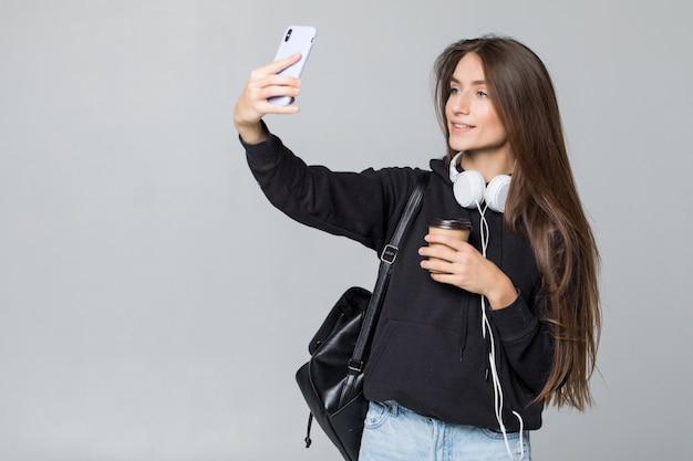 Junge schöne studentin mit rucksack macht selfie isoliert auf weißer wand im studio