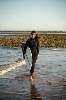 Junge schöne surferin am strand bei sonnenuntergang