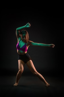 Junge schöne tänzerin, die auf schwarz tanzt