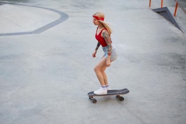 Junge schöne tätowierte dame mit blonden haaren in einem roten t-shirt und jeansshorts, mit einem gestrickten kopftuch auf dem kopf, genießt den tag und überfällt auf skateboard im skatepark.
