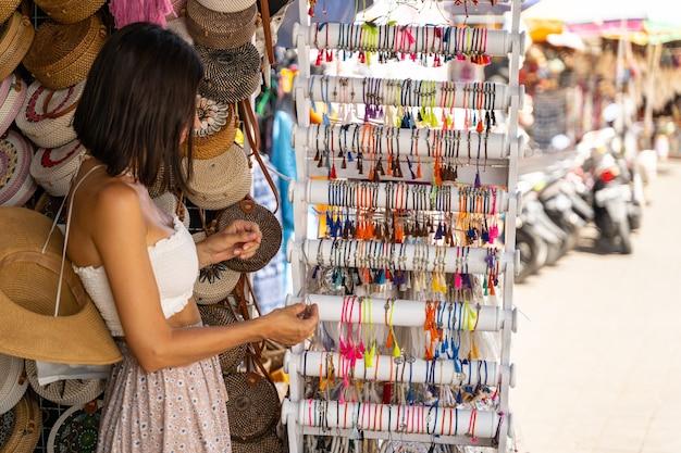 Junge schöne touristin wählt souvenirs im straßenladen aus und schaut sich farbarmbänder an lokales souvenirkonzept