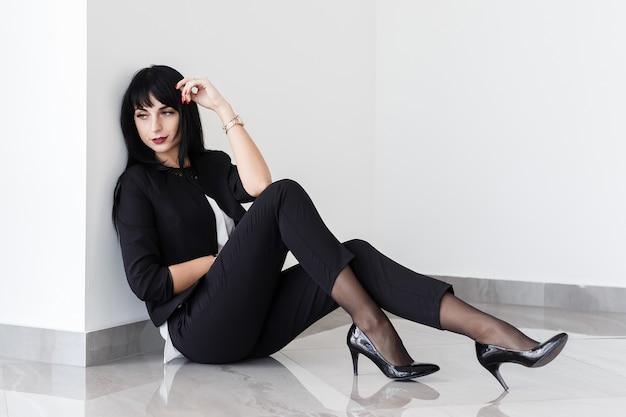 Junge schöne traurige brunettefrau kleidete in einem schwarzen anzug an, der auf einem boden in einem büro sitzt.