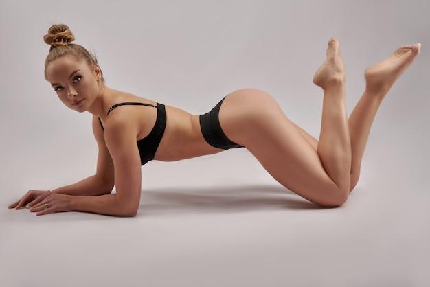 Junge schöne turnerin in sportkleidung. training, gymnastikelement, akrobatik an einer weißen wand. sportliche motivation, stretching, werbebanner