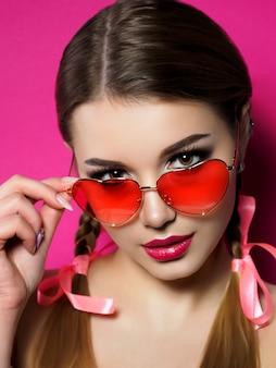 Junge schöne verspielte frau schaut über ihre herzförmige rote brille. valentinstag, liebe oder thema party konzept. smokey augen und rote lippen make-up.