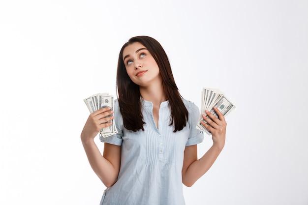 Junge schöne verträumte nachschlagende geschäftsfrau, die geld in beiden händen über weißer wand hält
