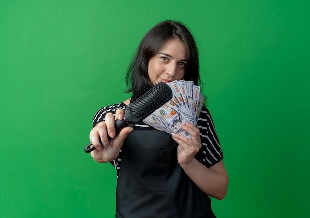 Junge schöne weibliche friseurin in der schürze, die bargeld hält, die haarbürste zeigt, die zuversichtlich über grün lächelt