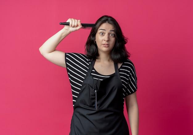 Junge schöne weibliche friseurin in der schürze, die haarbürste hält, die ihr haar über rosa kämmt