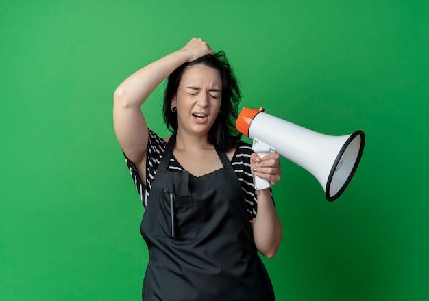 Junge schöne weibliche friseurin in der schürze, die megaphon hält, das verwirrt mit der hand auf ihrem kopf steht, der über grüner wand steht
