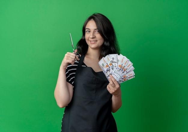 Junge schöne weibliche friseurin in der schürze, die schere hält, die bargeld mit selbstbewusstem lächeln über grün zeigt