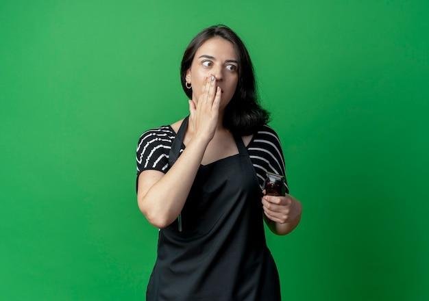 Junge schöne weibliche friseurin in der schürze hält trimmer, der mit hand nahe mund flüstert, der klatsch steht, der über grüner wand steht