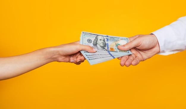 Junge schöne weibliche hand gibt der männlichen hand eines geschäftsmannes einen haufen geld für dienstleistungen