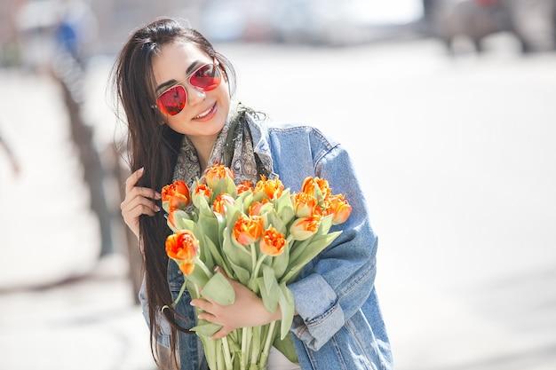 Junge schöne zeit der frau draußen im frühjahr. attraktiver mädchenabschluß herauf porträt. dame, die geschenke hält, präsentiert kästen. frau mit blumen. fröhliche frau hält tulpen.