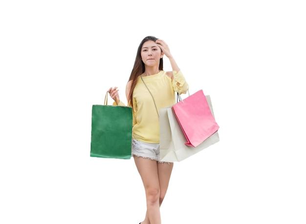 Junge schönheit asiatisches mädchen, das kleid gelb lässig mit einkaufskauf trägt und papiertüte hält, isoliert auf weißem hintergrund