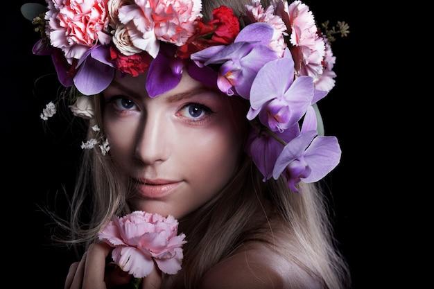 Junge schönheit des porträts im kranz von blumen