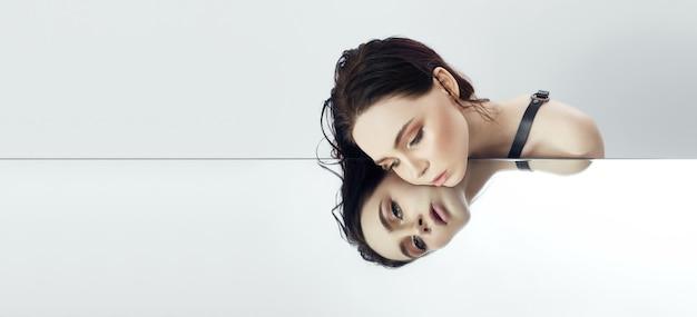 Junge schönheit des schönheitsgesichtes, die auf spiegel, natürliche make-uphautpflege, kopienraum liegt. mädchen sieht reflexion im spiegel. mode, schönheit, kosmetik, make-up, haare, schönheit, rabatte, verkäufe, copyspace