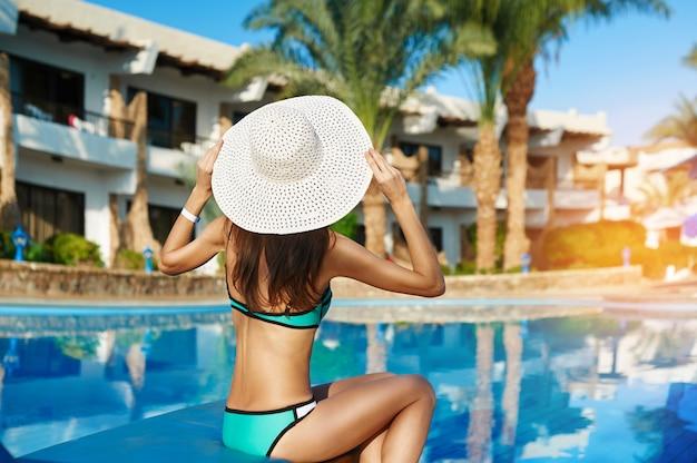 Junge schönheit, die auf sonnenruhesesseln durch swimmingpool im hotel im großen weißen hut sitzt