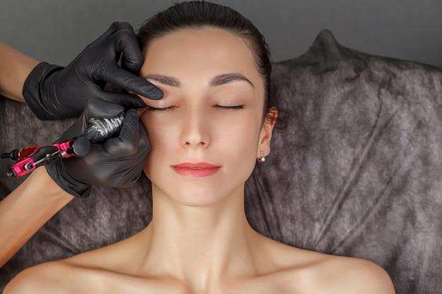 Junge schönheit, die dauerhaftes make-up im cosmetologiesalon macht