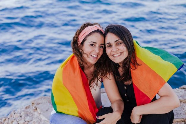 Junge schönheit, die draußen eine homosexuelle flagge des regenbogens hält