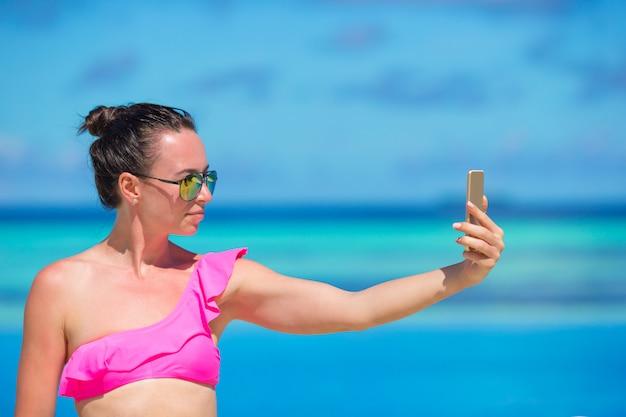Junge schönheit, die draußen selfie mit telefon während der strandferien nimmt