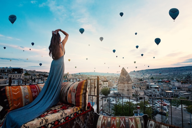 Junge schönheit, die elegantes langes kleid vor cappadocia-landschaft am sonnenschein mit ballonen in der luft trägt. truthahn.