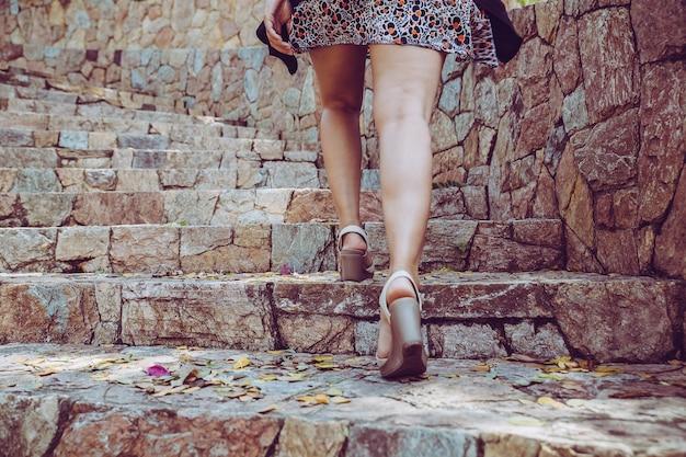 Junge schönheit, die herauf die steintreppe mit hintergrund geht. schritt für erfolgskonzept.