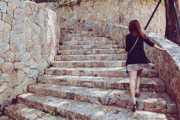 Junge schönheit, die herauf die steintreppe mit natürlichem hintergrund geht. schritt für erfolgskonzept.