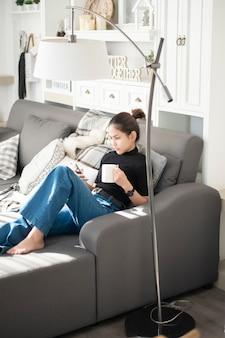 Junge schönheit, die sich zu hause auf sofa entspannt und intelligentes telefon verwendet