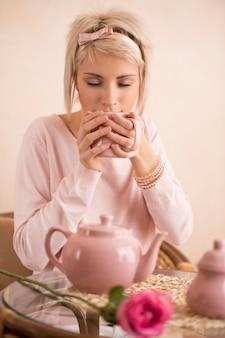Junge schönheit, die teeparty in der rosa weiblichen art hat