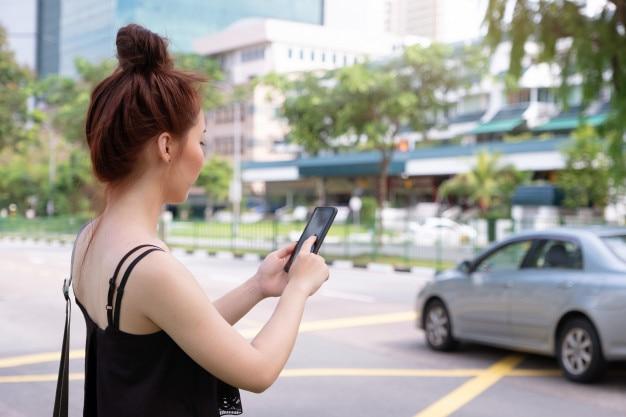 Junge schönheit, die telefon verwendet, um taxi in singapur zu ergreifen. neben der straße stehen