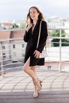 Junge schönheit frau, die auf balkon des cafés am sommertag entspannt