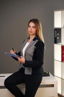 Junge schönheit im büro und in der jacke, die dokumente hält