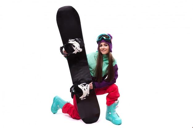 Junge schönheit im purpurroten skimantelstand auf knie- und griffsnowboard
