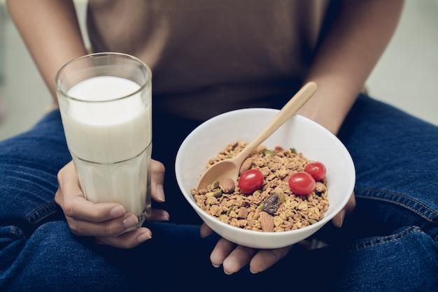 Junge schönheit mach s gut ihre gesundheit, indem sie milch mit granola mit mehreren körnern am morgen isst