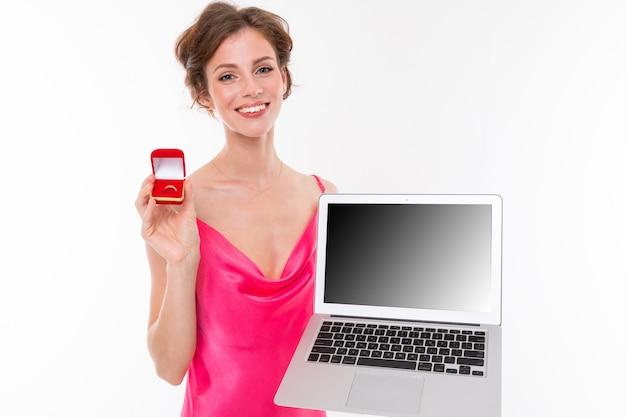 Junge schönheit mit dem gewellten braunen ausgebesserten haar, sauberer haut, den flachen zähnen, schönem lächeln, im rosa trikot, hält einen trainingsringkasten und einen laptop