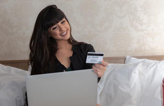 Junge schönheit mit kreditkarte und laptop-computer, on-line-einkaufskonzept.