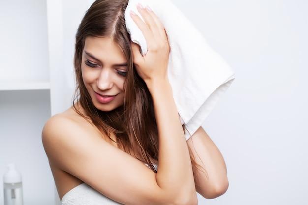 Junge schönheit wischt sich nach der haarpflege die haare mit einem weichen handtuch ab.