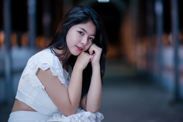 Junge schönheits-frau im weißen kleid des nachtlichtes