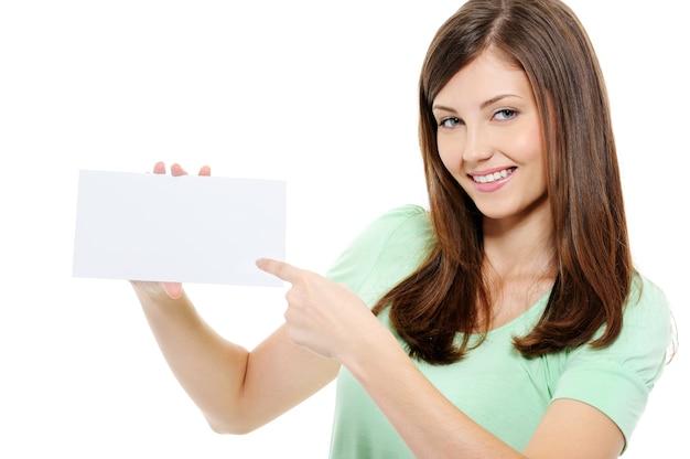 Junge schönheitsfrau, die auf die leere weiße karte zeigt - lokalisiert auf weiß