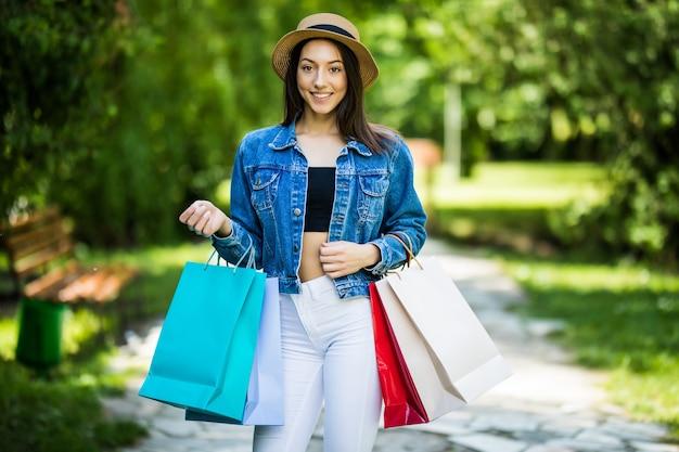 Junge schönheitsfrau, die einkaufstaschen hält, die im stadtpark nach besuchsgeschäft gehen